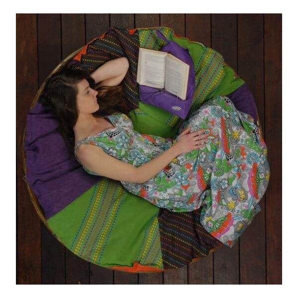 Kirjatyyny, kirjatuki, lukuteline Bookseat. Käyttökuvassa tyttö käpertyneenä isolla tyynyllä kirjaa lukien.