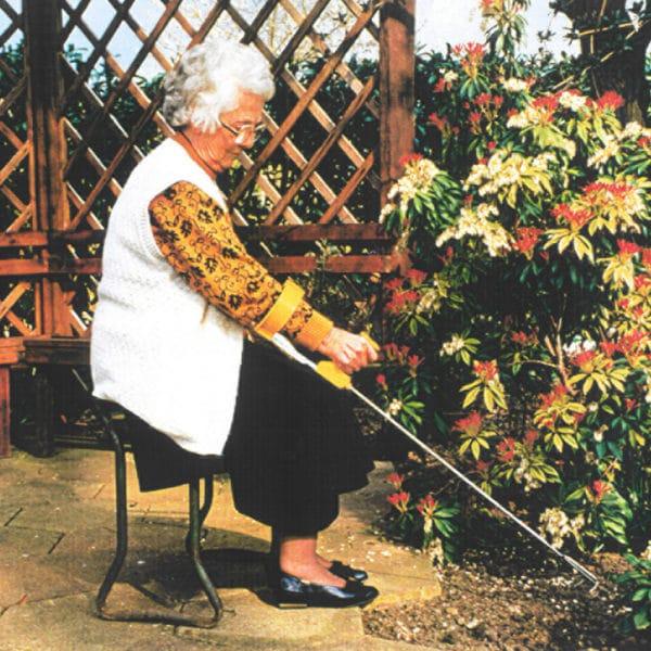 Puutarhanhoitoa tuolissa istuen. Kätevä istutushara pitkävartinen ergonominen Easi-Grip PLR-C ei rasita rannetta e puutarhassa työskennellessä.