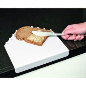 Leikkuulauta reunoilla. Laudan sivuissa rivi muovitappeja, jotka pitävät leipäpalan paikallaan silloin kun käytössä on vain toinen käsi.